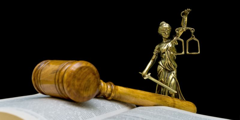 Statue of justice on a black background. Gavel and law book in the foreground out of focus.
