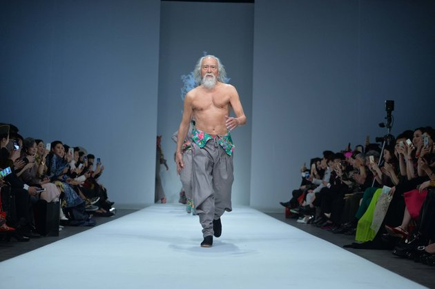 """79-year-old Chinese actor Wang Deshun displays a new creation by Chinese fashion designer Sheguang Hu at the Sheguang Hu fashion show during the China Fashion Week Fall/Winter 2015 in Beijing, China, 25 March 2015."""