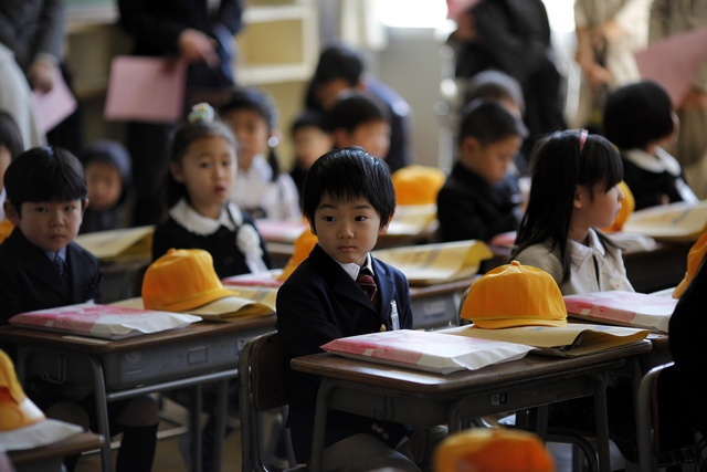 Children sit inside a classroom on their first day of school at Shimizu elementary school in Fukushima, northern Japan April 6, 2011. Over 70 schools began their regular classes on Wednesday in the city of Fukushima, after the earthquake and tsunami that hit the country on March 11. REUTERS/Carlos Barria (JAPAN - Tags: DISASTER EDUCATION SOCIETY)